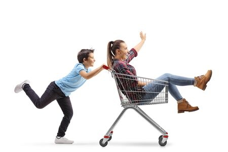 Full length profile shot of a boy pushing his teenage sister in a shopping cart isolated on white background