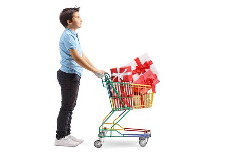 Full length profile shot of a boy with a shopping cart full of wrapped presents isolated on white background
