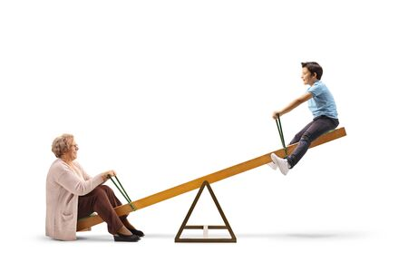 Full length profile shot of a grandson playing on a seesaw with grandmother isolated on white background