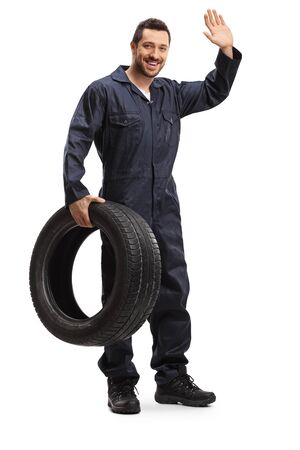 Full length portrait of a mechanic holding a vehicle tire and waving isolated on white background