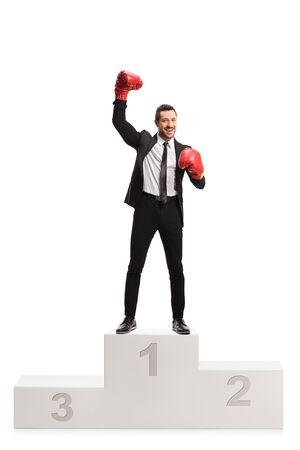 Full length portrait of a man in a suit with boxing gloves posing on a winners pedestal isolated on white background