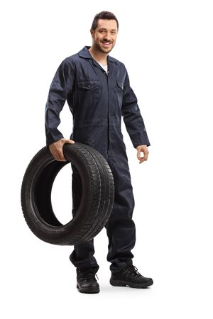 Full length portrait of a mechanic smiling and holding a tire isolated on white background Stock fotó