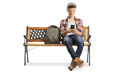Männlicher Teenager, der auf einer Bank sitzt und ein auf Weiß isoliertes Mobiltelefon benutzt Standard-Bild