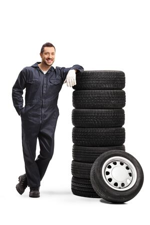 Full length portrait of a car repair worker posing with a pile of tires isolated on white 写真素材