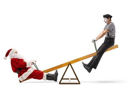 Full length profile shot of Santa Claus on a seesaw with a mime isolated on white