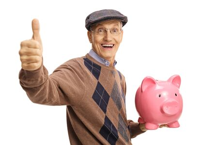Happy elderly man holding a piggy bank and showing thumb up isolated on white