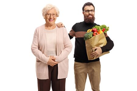 Senior woman and a younger bearded man with fruits and vegetables in a paper bag isolated on white Stock fotó