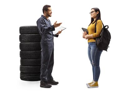 Full length profile shot of a female student and an auto mechanic having a conversation next to a pile of car tires isolated on white