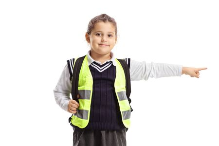 Little schoolgirl wearing safety vest standing and pointing isolated on white Stockfoto
