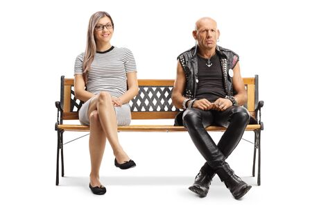 Full length portrait of a young blond woman and a grumpy punker sitting on a bench isolated on white background