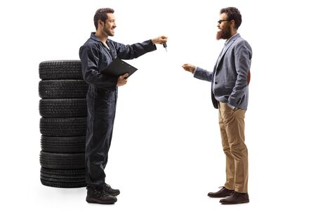 Full length profile shot of an auto mechanic with a pile of tires giving a car key to a bearded man isolated on white background