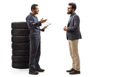 Full length profile shot of an auto mechanic with a pile of tires talking to a bearded man isolated on white background