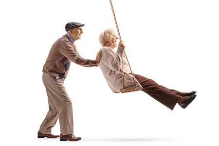 Full length profile shot of a senior man pushing his wife on a swing isolated on white background