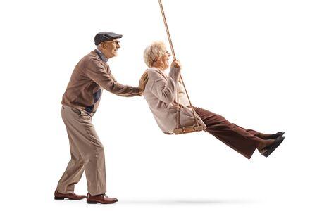 Pełnej długości zdjęcie profilowe starszego mężczyzny popychającego żonę na huśtawce na białym tle