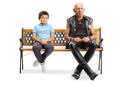 Full length portrait of a punk man sitting on a bench with a little boy isolated on white background