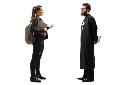 Full length profile shot of a young female student talking to a priest isolated on white background
