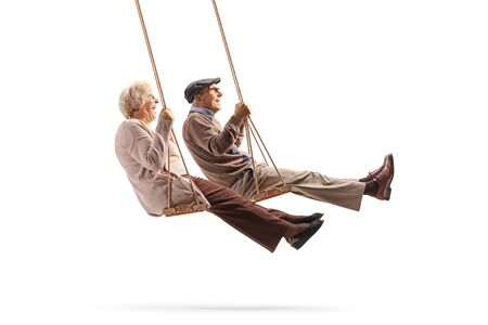 Full length profile shot of a elderly man and woman swinging on wooden swings isolated on white background