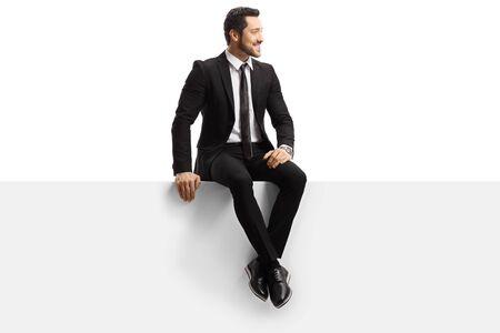 Junger gutaussehender Mann in einem Anzug sitzt auf einem Panel isoliert auf weißem Hintergrund