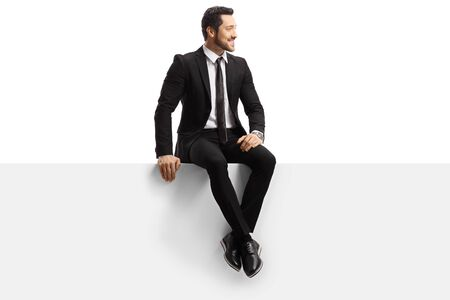 Young handsome man in a suit sitting on a panel isolated on white background