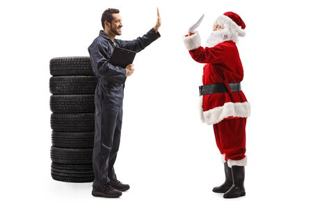 Full length profile shot of an auto mechanic gesturing high five with a Santa Claus isolated on white background Stock Photo