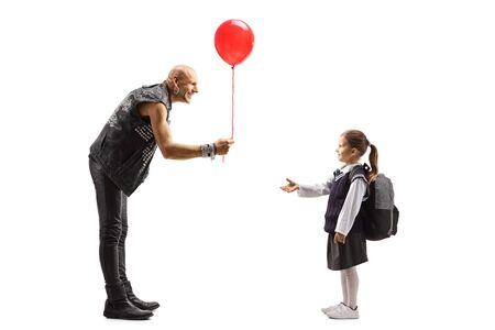 Full length shot of a punker in leather clothes giving a red baloon to a schoolgirl isolated on white background