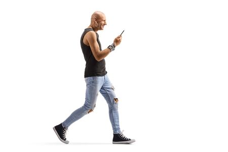 Full length profile shot of a bald male hispter walking and holding a mobile phone isolated on white background Reklamní fotografie