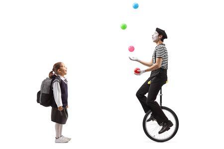 Disparo de longitud completa de una colegiala mirando un mimo haciendo malabares en un monociclo aislado sobre fondo blanco. Foto de archivo