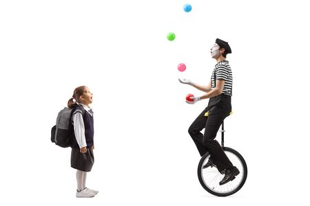 Full length shot of a schoolgirl looking at a mime juggling on a unicycle isolated on white background Stock Photo