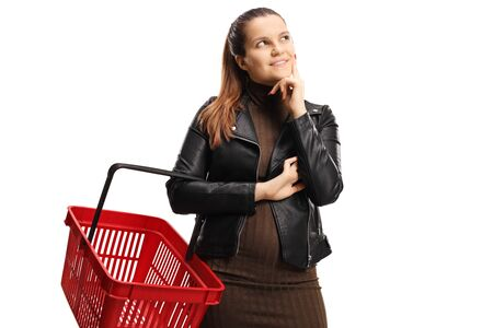 Young pensive woman holding a shopping basket isolated on white background