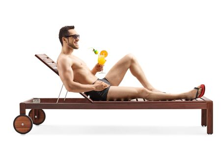Full length shot of a handsome young man sunbathing and drinking a cocktail isolated on white background Stockfoto