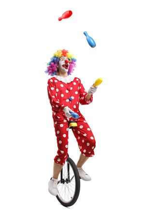 Clown on a unicycle juggling isolated on white background