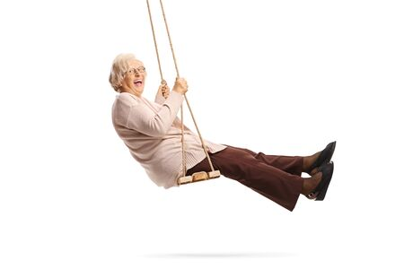 Senior lady swinging on a swing and laughing isolated on white background
