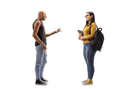 Full length profile shot of a male hipster talking to a female student holding books isolated on white background