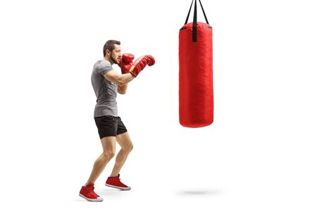 Full length shot of a young athlete training box with a punching bag isolated on white background