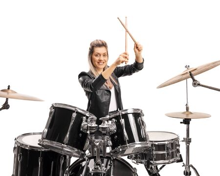 Beautiful female drummer with a drumkit and drumsticks isolated on white background