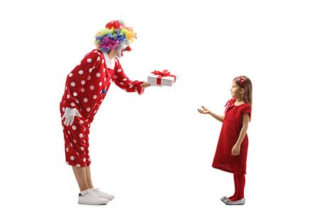 Full length profile shot of a clown giving a present to a girl isolated on white background