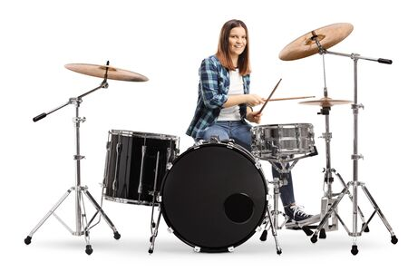 Young female learning to play drums isolated on white background