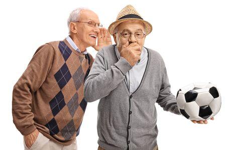 Uomo anziano che sussurra ad un amico che tiene in mano un pallone da calcio sgonfio e ride isolato su bianco