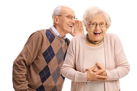 Hombre mayor susurrando a una mujer mayor aislada sobre fondo blanco