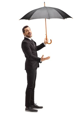 Full length shot of a man in a black suit with umbrella checking if it is raining isolated on white background Stock fotó