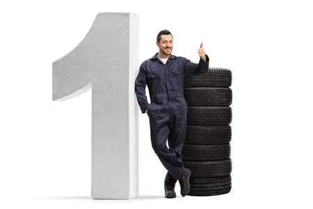 Full length portrait of a mechanic posing with a pile of car tires and a big number one, showing thumbs up isolated on white