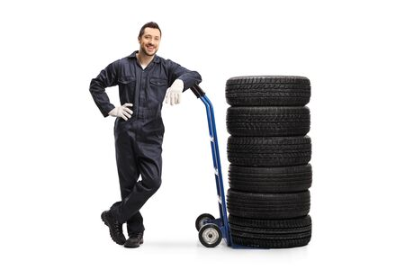 Full length portrait of an auto mechanic with a pile of tires on a hand truck isolated on white background