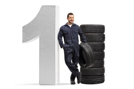 Full length portrait of an auto mechanic leaning on a big number one and holding a car tire isolated on white background