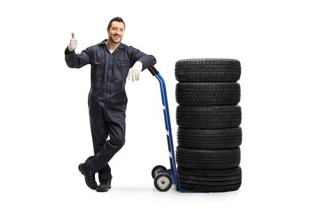 Full length portrait of an auto mechanic leaning on a hand truck with tires and showing thumbs up isolated on white background
