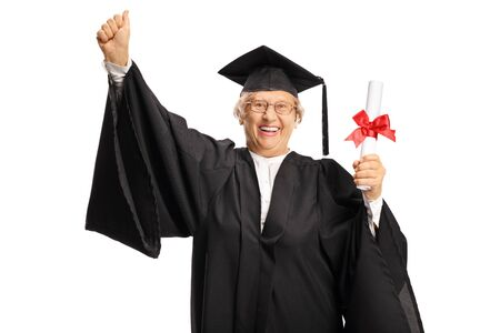Happy elderly woman in a graduation gown holding a diploma and gesturing happiness with hand isolated on white background