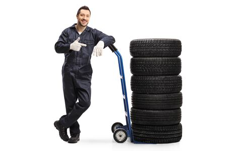 Full length portrait of a car mechanic in a uniform standing with tires on a hand truck isolated on white background