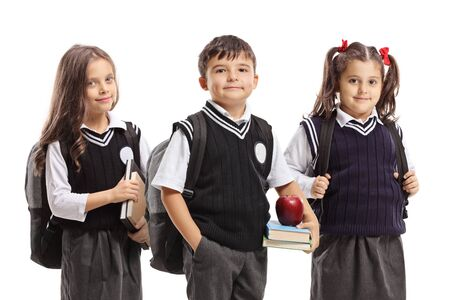 Two girls and one boy in school uniforms posing isolated on white background