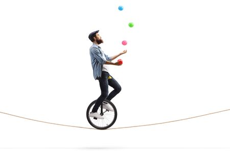 Full length profile shot of a bearded male hipster juggler with balls riding a unicycle on a rope isolated on white background Stock Photo