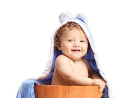 Smiling baby boy in a wooden bucket with a towel above his head isolated on white background Zdjęcie Seryjne