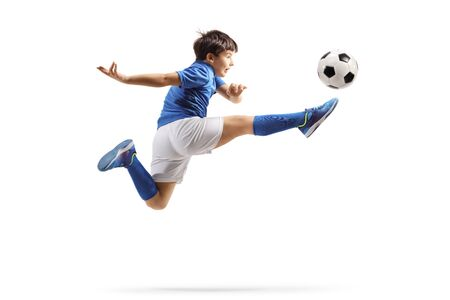 Boy in a sports jersey jumping and kicking a soccer ball isolated on white background
